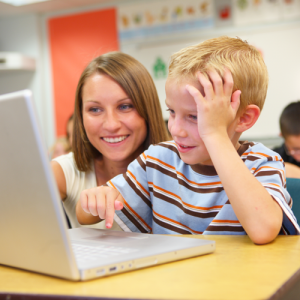 Teacher with kid at a computer